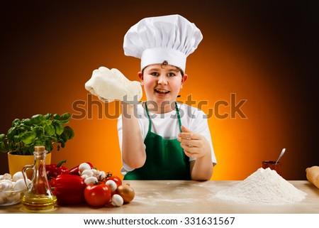 Boy making pizza dough  - stock photo