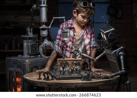 Boy mechanic looks like two robots play a game of chess in the studio in the evening - stock photo