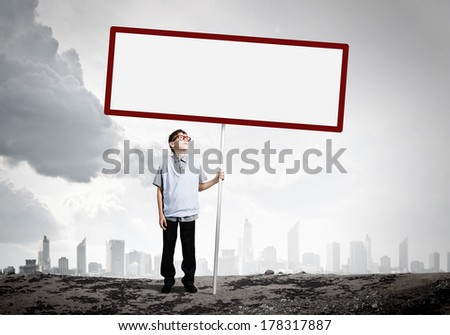 Boy of school age in glasses holding blank white banner - stock photo