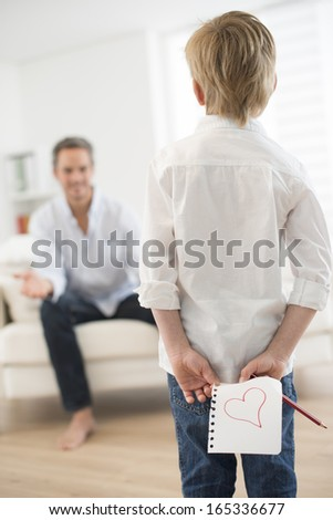 boy offering a drawing heart to his father - stock photo