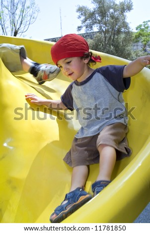 boy on a yellow playground slide - stock photo