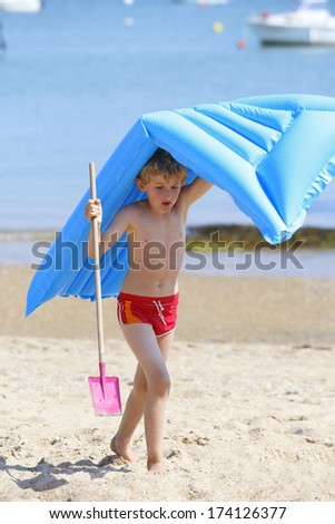 Boy on beach with scoop and mattress - stock photo