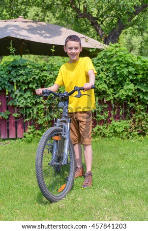 boy on bike in summer day - stock photo