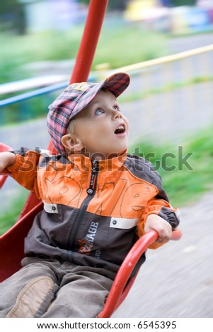 Boy on carousel at amusement park. Motion - stock photo