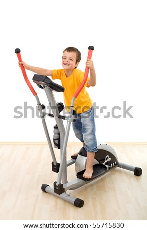 Boy on elliptical trainer fitness equipment having fun - stock photo