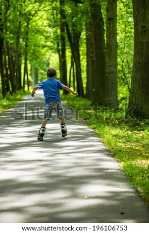 boy on inline skates, rolling through the park - stock photo