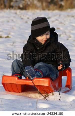 boy on sledge front view - stock photo