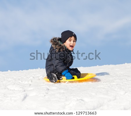 Boy on sleigh. Sledding at winter time - stock photo