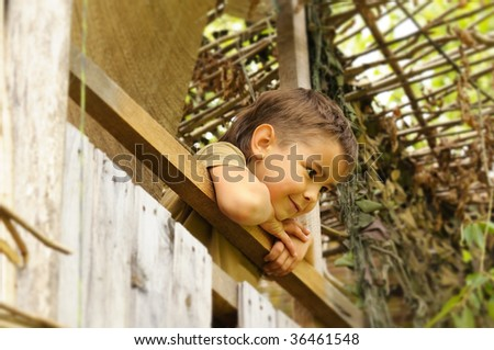 Boy on the balcony looking at someone downstairs - stock photo