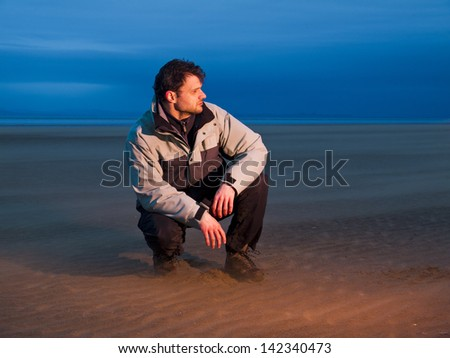 Boy on the beach during storm. Taken with red flash. - stock photo