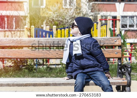 boy on the street in  mother's sunglasses - stock photo