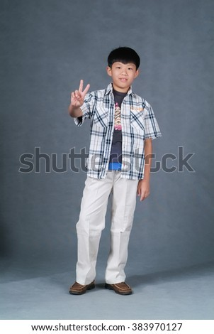 boy or asian chinese little boy doing victory gesture on background - stock photo