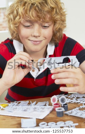 Boy Painting Model Car At Home - stock photo
