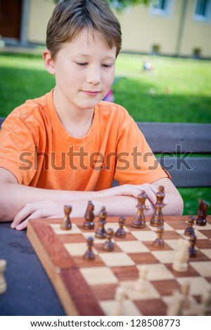 Boy play Chess with Concentration - stock photo