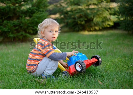 Boy play with mower toy. - stock photo