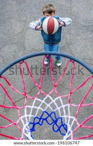 boy playing basketball photographed from above the ring - stock photo