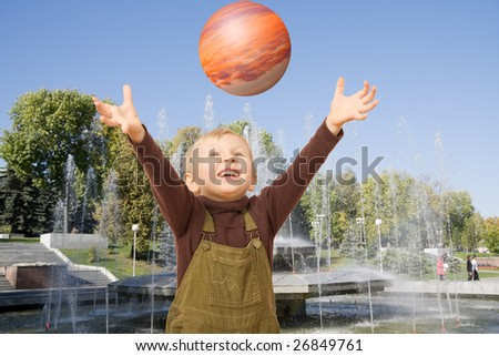 boy playing catch before fountain in early fall - stock photo