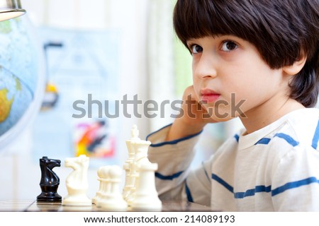 boy playing chess and pondered the next move - stock photo