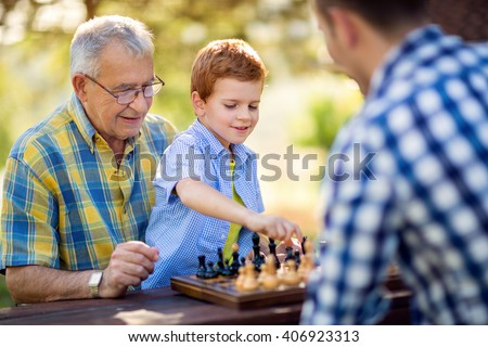 boy playing chess on the table in the park - stock photo