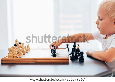 Boy playing chess with black peace, copy space - stock photo