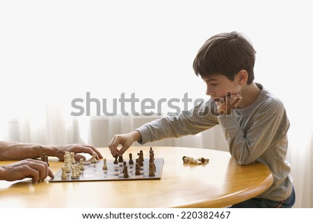 Boy playing chess with elderly man - stock photo