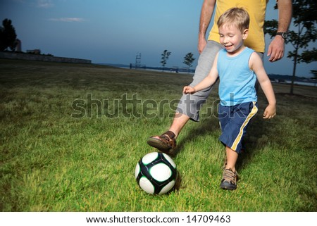 Boy playing football with his dad outdoors on green grass field - stock photo