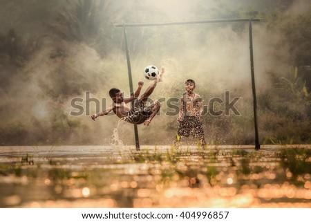 Boy playing football with kicking soccer ball  - stock photo