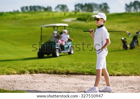 Boy playing golf and hitting from bunker  - stock photo