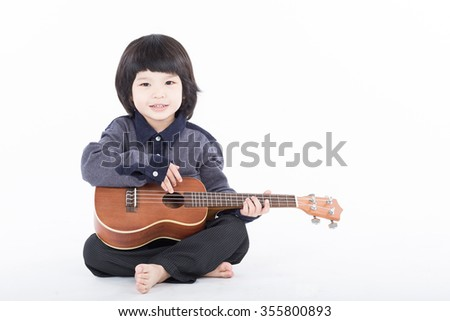 Boy playing guitar on white background - stock photo