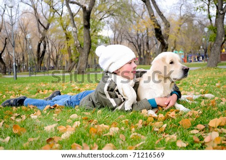 Boy playing in autumn park with a golden retriever. - stock photo