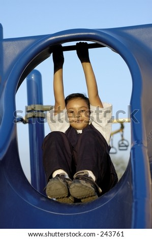 Boy playing in playgrond. Climbing rope. Natural light at sunset. - stock photo