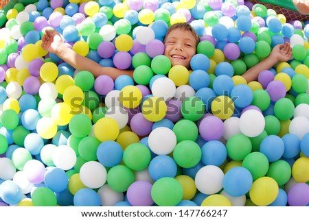 boy playing in playground colourful ball pool - stock photo