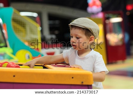 Boy playing in the games attraction at an amusement park - stock photo