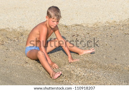 Boy playing in the sand on the beach - stock photo