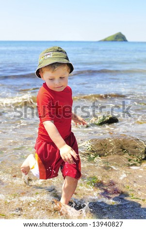 Boy playing in the sea. - stock photo