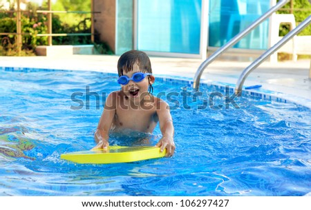 Boy playing in the swimming pool - stock photo