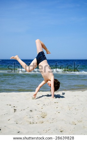 Boy playing on beach - stock photo