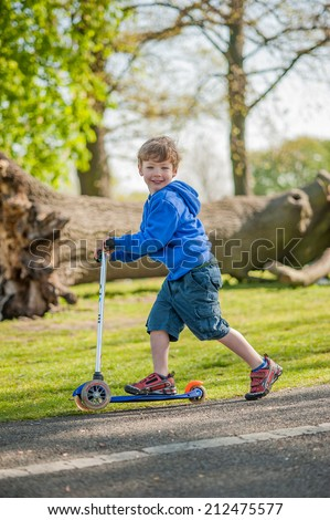 Boy playing on his scooter in the local park. - stock photo