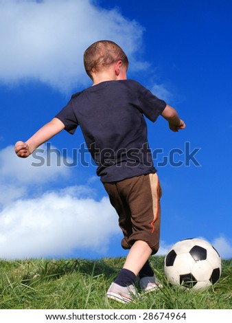 Boy playing soccer against the sky - stock photo