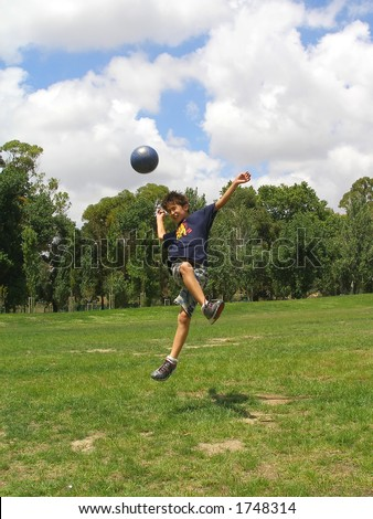 Boy playing soccer in a green grass field with blue sky above - stock photo