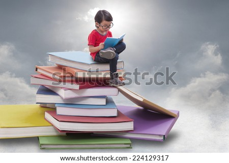 Boy playing tablet and sitting on pile of books  - stock photo