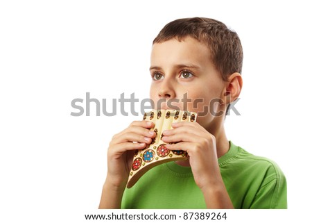 Boy playing the panpipe, isolated on white background - stock photo