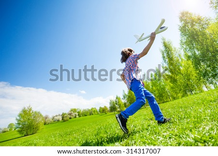 Boy playing with airplane toy during running in the green meadow during summer day in the park - stock photo