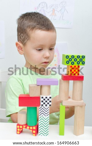 Boy playing with blocks in kindergarten - stock photo