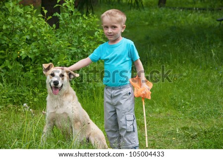 Boy playing with dog in the forest - stock photo