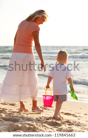 Boy playing with grandmother on the golden beach - stock photo