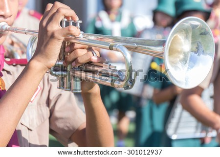 boy playing with his trumpet on center field in the sun - stock photo