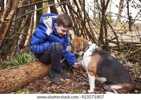Boy playing with pet dog under a shelter of tree branches - stock photo