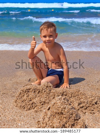 Boy playing with sand on the beach - stock photo