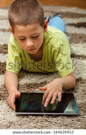 Boy playing with tablet pc - stock photo